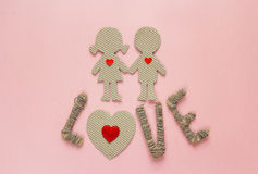 Cardboard silhouettes girl and boy with hearts and the word love Royalty Free Stock Photography