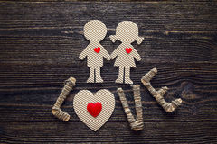 Cardboard silhouettes girl and boy with hearts and the word love Royalty Free Stock Images