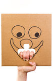 Cardboard with sketch of smiling face in hand Royalty Free Stock Photos