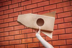 Cardboard space rocket in hand against brick wall royalty free stock image