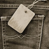 Cardboard tag on jeans Royalty Free Stock Photography