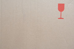 Cardboard texture with fragile symbol. Brown cardboard texture with red glass - fragile symbol stock photography