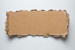 Cardboard torn piece. On white background royalty free stock photography