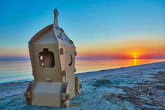 Cardboard toy spaceship at sea coast and sunset Stock Image