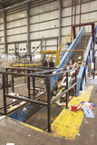 Cardboard travelling up conveyor belt of recycling machinery Royalty Free Stock Photography