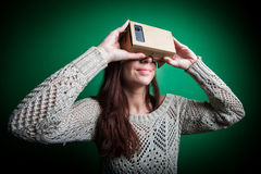 Cardboard virtual reality. Color shot of a young woman looking through a cardboard, a device with which one can experience virtual reality on a mobile phone Stock Photos