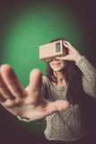 Cardboard virtual reality. Color shot of a young woman looking through a cardboard, a device with which one can experience virtual reality on a mobile phone Royalty Free Stock Images