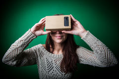 Cardboard virtual reality. Color shot of a young woman looking through a cardboard, a device with which one can experience virtual reality on a mobile phone Royalty Free Stock Photography