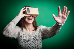 Cardboard virtual reality. Color shot of a young woman looking through a cardboard, a device with which one can experience virtual reality on a mobile phone Stock Photo