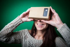 Cardboard virtual reality. Color shot of a young woman looking through a cardboard, a device with which one can experience virtual reality on a mobile phone Royalty Free Stock Photos