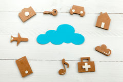 Cardboard web icons  and blue cloud on blue background. Set of web icons or graphical illustrations cut from cardboard and placed on blue wooden background Royalty Free Stock Image