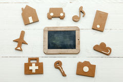 Cardboard web icons and an old blackboard on white background. Set of web icons or graphical illustrations cut from cardboard and placed on white wooden Stock Photo