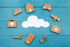 Cardboard web icons  and white cloud on blue background. Set of web icons or graphical illustrations cut from cardboard and placed on blue wooden background Stock Photo