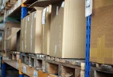 Cardboards met producten in het grote pakhuis Stock Fotografie