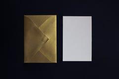 Carde la invitación y el sobre de oro en el fondo negro fotos de archivo
