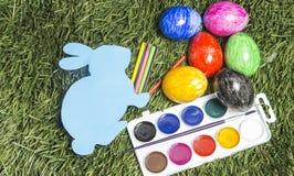 Carde o coelho com os marcadores coloridos nele mão do ` s e e ovos na grama Imagem de Stock Royalty Free