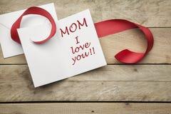 Cardez je t'aime la maman et le ruban rouge sur le fond en bois Photographie stock libre de droits