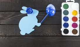 Cardez le lapin avec le marqueur là-dessus main du ` s et rose de bleu là-dessus tête du ` s, peignant l'oeuf dans le bleu Photographie stock libre de droits