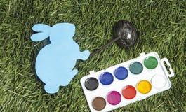 Cardez le lapin avec le marqueur là-dessus main du ` s, peignant l'oeuf dans le noir photo libre de droits