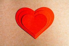Cardez pendant un jour de Valentine Coeur de papier de trois rouges Image stock