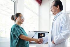 Cardiólogo y cirujano que sacuden las manos foto de archivo