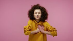 Cardiac problems. Young fatigued woman afro hairstyle in hoodie clasping chest, feeling acute pain, heart attack