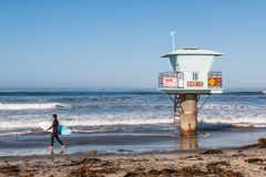 Lone Male Surfer on San Elijo State Beach in San Diego County. CARDIFF, CALIFORNIA/USA - APRIL 14, 2018:  A lone male surfer carries a surfboard past a lifeguard Stock Photos
