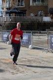 CARDIFF, PAÍS DE GALES - 23 DE MARZO: Hombre no identificado que corre en ayuda Foto de archivo libre de regalías