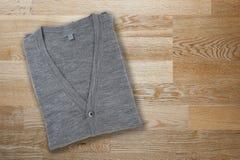 cardigan gris sur le fond en bois photos libres de droits