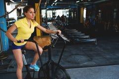 Cardio allenamento su una bici fissa Ragazza nel randello di forma fisica Fotografia Stock