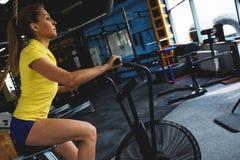 Cardio allenamento su una bici fissa Ragazza nel randello di forma fisica Immagini Stock