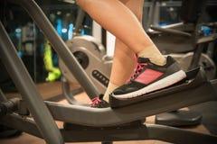 Cardio- exercício do close up dos jovens que dão certo em um instrutor elíptico no gym fotos de stock
