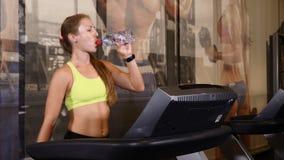 Cardio- exercícios na trilha de passeio no gym Mulher desportiva nova que faz a água potável dos exercícios 4K filme