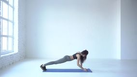 Cardio exercises. The sporty trainer is warming up by doing the up down plank in white studio. 4k footage. Cardio exercises. The sporty trainer is warming up by stock video footage