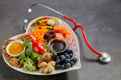 Cardio health food concept. With stethoscope next to hearth-shaped white dish full of healthy organic food ingredients. Studio shot close-up on grey background Stock Image