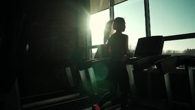 Cardio on the treadmill. exercises for weight loss. silhouette of a girl on a treadmill. young sporty girl running on. Girl running on the treadmill in the stock video footage