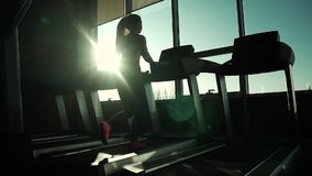 Cardio on the treadmill. exercises for weight loss. silhouette of a girl on a treadmill. young sporty girl running on. Girl running on the treadmill in the stock footage