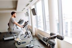 Cardio- treinamento do homem em uma bicicleta imagem de stock
