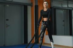 Cardio- triagem A mulher bonita contratou com cordas no gym fotos de stock royalty free