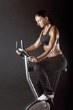 Cardio workout. Athletic woman exercising workout on a stationary bike Royalty Free Stock Photos