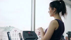 Cardio workout, beautiful woman drinks beverage from plastic bottle during training in fitness center. Against of a panoramic window stock video footage