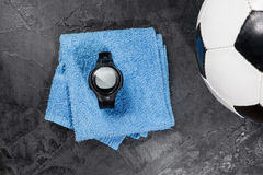 Cardiofrequenzimetro sull'asciugamano blu vicino a pallone da calcio Immagini Stock