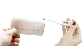 Cardiogram and an electronic thermometer in women's hands Royalty Free Stock Photography