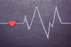 The cardiogram of the heart is painted with chalk on a blackboard. Concept of Love. Valentine`s Day stock images