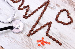 Cardiogram line of coffee grains, stethoscope and supplement pills, medicine and healthcare concept Stock Photo