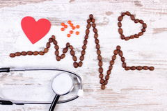 Cardiogram line of coffee grains, stethoscope and supplement pills, medicine and healthcare concept Stock Photos