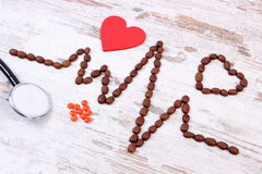 Cardiogram line of coffee grains, stethoscope and supplement pills, medicine and healthcare concept Royalty Free Stock Image