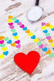 Cardiogram line of paper hearts and stethoscope on wooden background, medicine and healthcare concept Stock Photo