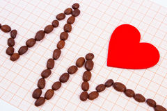 Cardiogram line of roasted coffee grains and red heart, medicine and healthcare concept Royalty Free Stock Photos