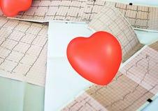 Cardiogram met klein rood hart op de lijstachtergrond stock fotografie